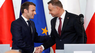 French President Emmanuel Macron and Polish President Andrzej Duda shake hands during a news conference after their meeting, in Warsaw, Poland February 3, 2020.