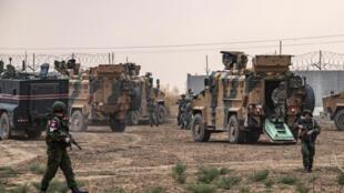 Soldados rusos observan cómo los vehículos militares turcos se preparan para cruzar la frontera con Turquía después de patrullar con las fuerzas rusas, en el campo de la ciudad de Darbasiyah, en la provincia de Hasakeh, en el noreste de Siria, el 1 de noviembre de 2019. -