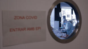 A healthcare worker in a protective suit attends to a COVID-19 coronavirus patient at a hospital in Barcelona