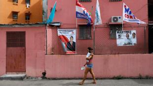 Una mujer camina junto a las banderas del Partido Revolucionario Democrático (PRD) antes de las elecciones generales en la Ciudad de Panamá, Panamá , 28 de abril de 2019.