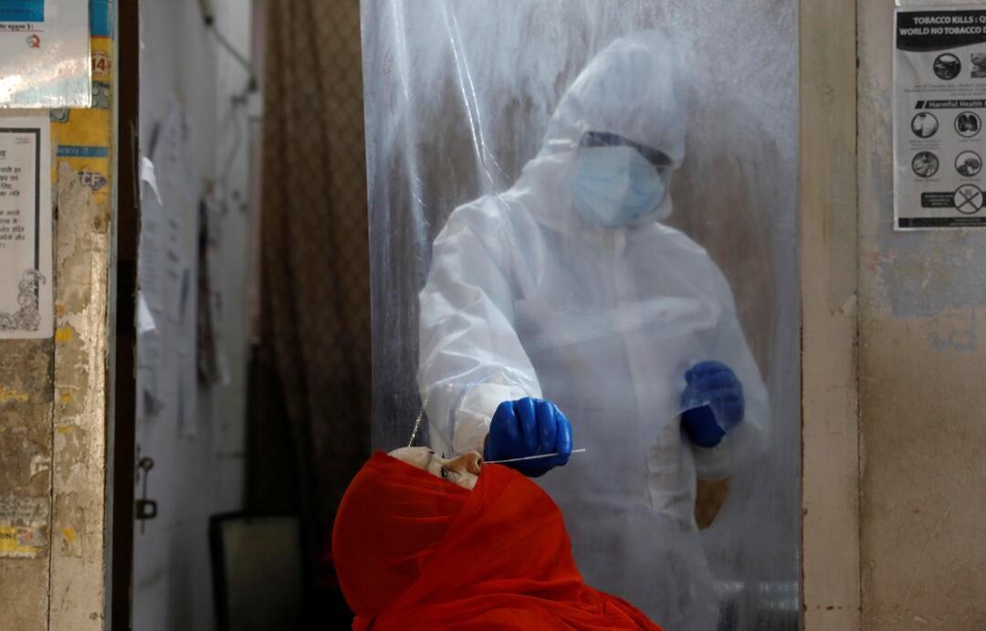 Un trabajador de la salud con equipo de protección personal mientras recolecta una muestra con un hisopo de una mujer en un centro de salud local para realizar pruebas de Covid-19 en Nueva Delhi, India, el 27 de junio de 2020.