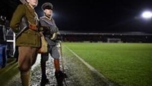 "People in military WWI uniforms watch the ""Game of Truce"", a recreation of a First World War Christmas truce football match, in Aldershot, west of London, on December 17, 2014"