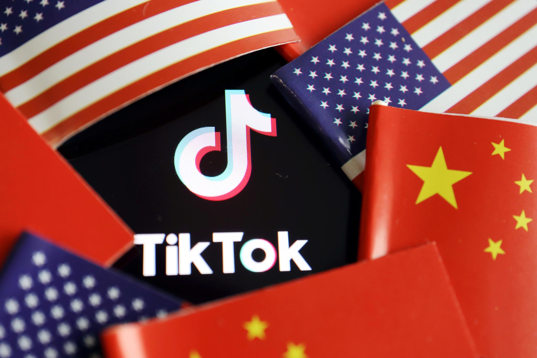 Washington accuse TikTok d'espionnage au profit de Pékin depuis des mois, sans apporter des preuves pour autant. Ici, les drapeaux américain et chinois entourant le logo du réseau social, le 16 juillet 2020.