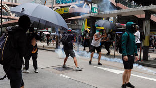 Protesters react to tear gas during a march against Beijing's plans to impose national security legislation in Hong Kong, China on May 24, 2020.