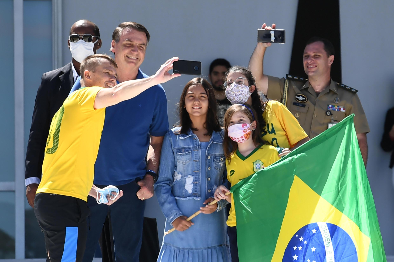El presidente de Brasil, Jair Bolsonaro, y su hija Laura posan para una foto con algunos de sus simpatizantes en pleno brote de coronavirus Brasilia, Brasil.