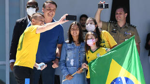 Brazilian President Jair Bolsonaro and his daughter Laura (C) pose for a selfie with supporters outside his residence in Brasilia on Sunday.