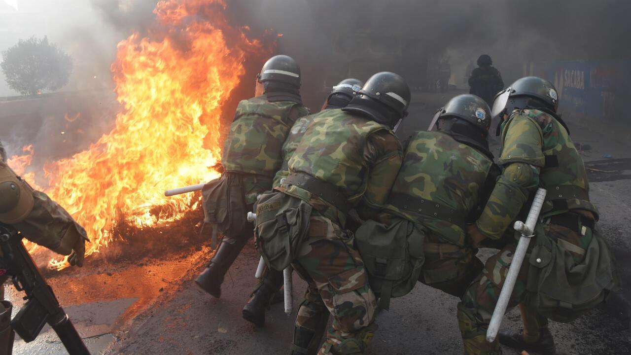 عناصر من الشرطة يحاولون إخماد حريق في كوتشابامبا (وسط) أحد معاقل الرئيس البوليفي السابق