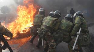 Des membres de la police militaire tentent de détruire des barricades, le 15 novembre 2019, dans la banlieue de Cochabamba.