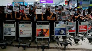 Les manifestants bloquent l'accès aux zones d'embarquement de l'aéroport international de Hong Kong, le 13août2019.