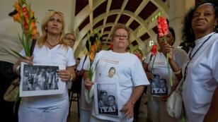 Les membres d'une association de défense des droits de l'Homme manifestent à La Havane, le 25 mars 2012, en tenant des photos de prisonniers politiques.