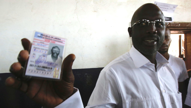 George Weah, exjugador de fútbol y candidato presidencial del Congreso para el Cambio Democrático muestra su tarjeta de votante en una mesa de votación en Monrovia, Liberia, 10 de octubre de 2017.