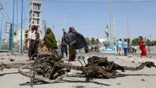 Las mujeres somalíes pasan frente a los restos de un automóvil involucrado en una explosión cerca de la residencia del presidente en Mogadiscio, Somalia, el 22 de diciembre de 2018.
