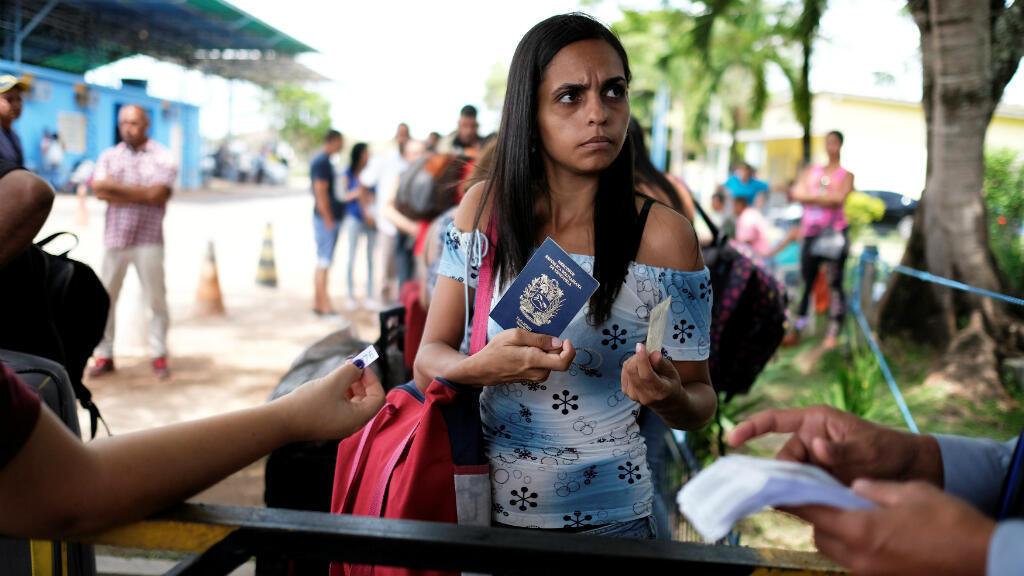 Una mujer venezolana muestra sus documentos de identidad en un control fronterizo del en el estado de Roraima en Brasil, 16 de noviembre de 2017.