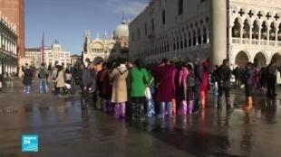 سياح في مدينة البندقية بإيطاليا التي ارتفع فيها منسوب المياه جراء الفياضانات