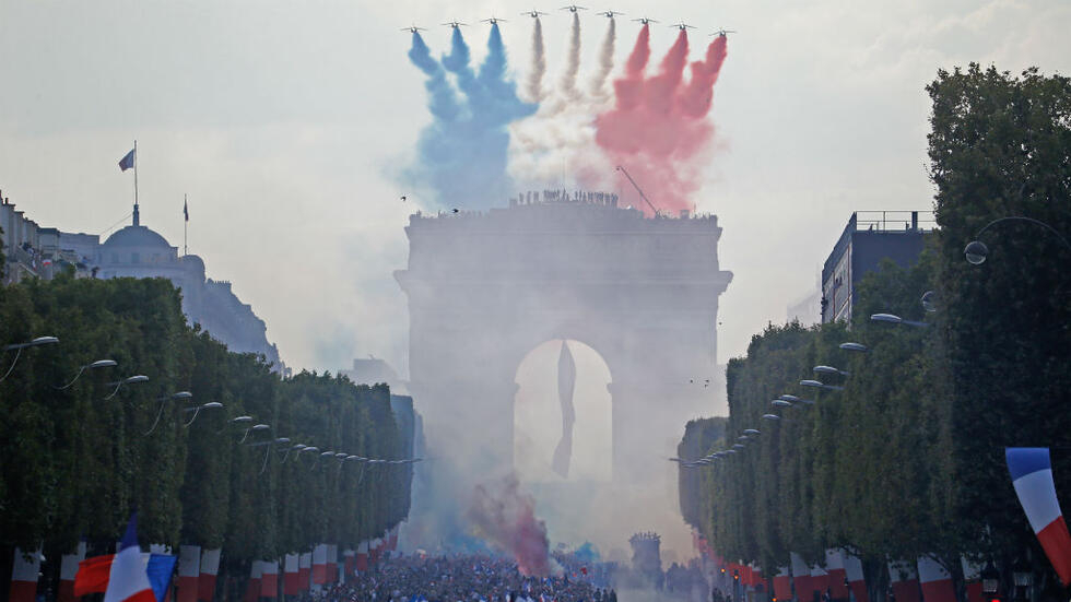 Patrouille de France jets fly over Paris's Champs-Élysées and Arc de Triomphe on July 16, 2018, as supporters welcome France football players home after their historic World Cup win.