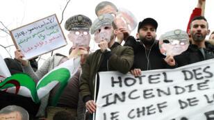 Des manifestants tiennent des masques à l'effigie du chef d'état major de l'armée, Ahmed Gaïd Salah, à Paris le 3mars2019.