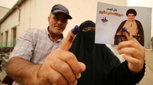 Un hombre y una mujer muestran la tinta en sus dedos después de votar en Basra, el 12 de mayo de 2018.