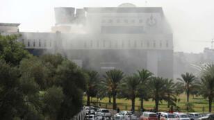 El humo asciende desde la sede de la petrolera libia National Oil Corporation (NOC), luego de que varias personas enmascaradas la atacaran en Trípoli, Libia, el 10 de septiembre de 2018.