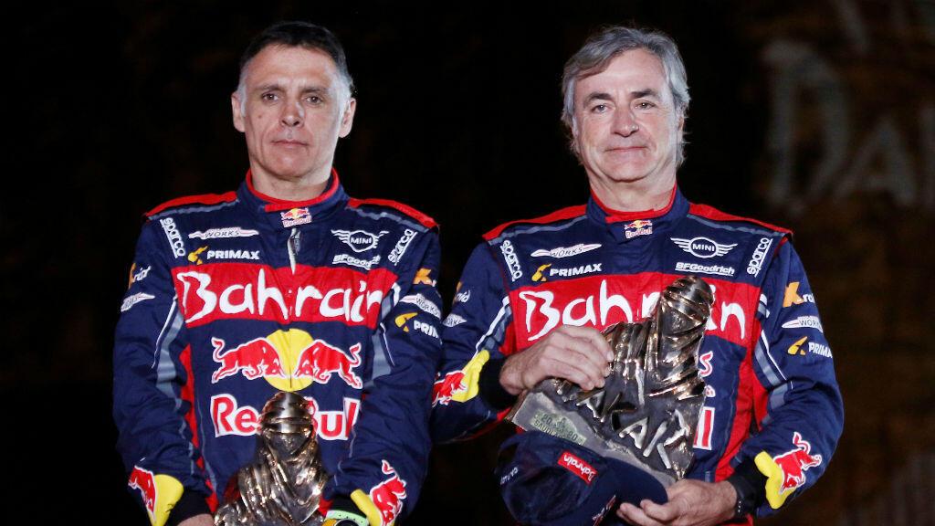 El español Carlos Sainz (derecha), posa con el trofeo del Dakar junto a su compatriota y copiloto Lucas Cruz. Qiddiya, Arabia Saudita, 17 de enero de 2020.
