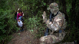 Un agente de la Unidad Táctica de la Patrulla Fronteriza de Estados Unidos detiene a una familia de migrantes después de que cruzaran la frontera entre México y EE. UU. de forma irregular en Texas, Estados Unidos, el 18 de octubre de 2018.