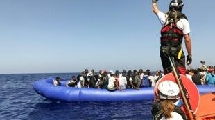 """أحد أفراد طاقم السفينة """"أوشن فايكينغ"""" قرب زورق مطاطي يقل 81 مهاجرا تم إنقاذهم قبالة ليبيا في 11 آب/أغسطس 2019"""