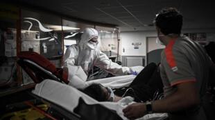 Des volontaires de la Croix Rouge prêtent main forte aux équipes du Samu pour transporter une patiente, le 5 mai 2020 à Paris
