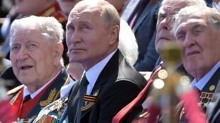الرئيس الروسي فلاديمير بوتين ومحاربين قدامى في عرض عسكري في 24 حزيران/يونيو2020