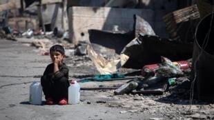 Un niño con dos latas de agua está sentado junto a refugios destruidos en un incendio en el campamento de refugiados de Moria, en la isla de Lesbos, Grecia, el 9 de septiembre de 2020.