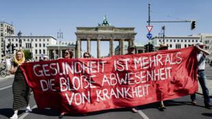 Des manifestants participent à la marche contre les mesures contraignantes liées au Covid-19, le 1er août à Berlin