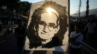 (ARCHIVOS) Esta foto de archivo tomada el 16 de marzo de 2013 en San Salvador muestra a personas marchando y sosteniendo un retrato del Arzobispo Oscar Romero asesinado, durante la conmemoración del 33 aniversario de su asesinato.