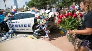 امرأة تضع الزهور على نصب تذكاري خارج مقر شرطة دالاس