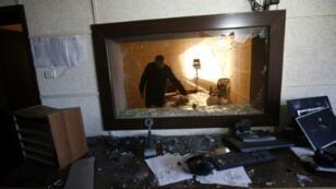 موظف في هيئة الإذاعة والتلفزيون الفلسطينية الحكومية يعاين الأضرار بعد اقتحام مقرها في غزة في 4 كانون الثاني/يناير 2019