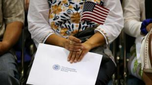 Una persona sostiene la bandera de su nuevo país y sus papeles de naturalización mientras es juramentada en una ceremonia de ciudadanía en Los Ángeles el 18 de julio de 2017.