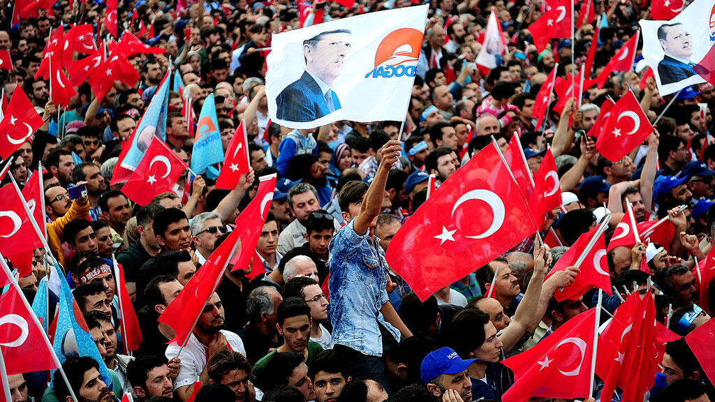 People wave Turkish flags, and one bearing the image of President Recep Tayyip Erdogan, at a rally in Istanbul on May 30.