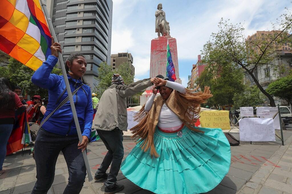 Activistas participan en un acto de protesta frente a la estatua de Cristóbal Colón, intervenida por manifestantes hoy, en La Paz (Bolivia). La estatua de Cristóbal Colón en la ciudad boliviana de La Paz apareció con pintadas este lunes, día en que se recuerda su llegada a América hace 528 años. El monumento en el centro de la ciudad andina tiene pintura roja en distintas partes y pintadas como una calavera con una cruz encima. El nombre de Colón aparece tachado en el monumento de mármol, en el que no se aparecía alguna pintada reivindicativa sobre este hecho.