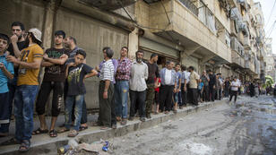 Les habitants d'un quartier d'Alep tenu par les rebelles doivent faire des queues interminables pour acheter du pain, comme ici le 12 juillet 2016.
