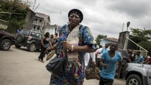 Une femme court après des tirs de sommation de la police devant la cathédrale de Kinshasa, le 12 janvier 2018.
