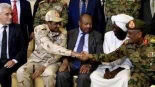 Le médiateur de l'Union africaine Mohamed El Hacen Lebatt, à gauche, aux côtés du général Mohamed Hamdan Dagalo qui serre la main au général Yaser al-Atta, à droite, le 5 juillet 2019.