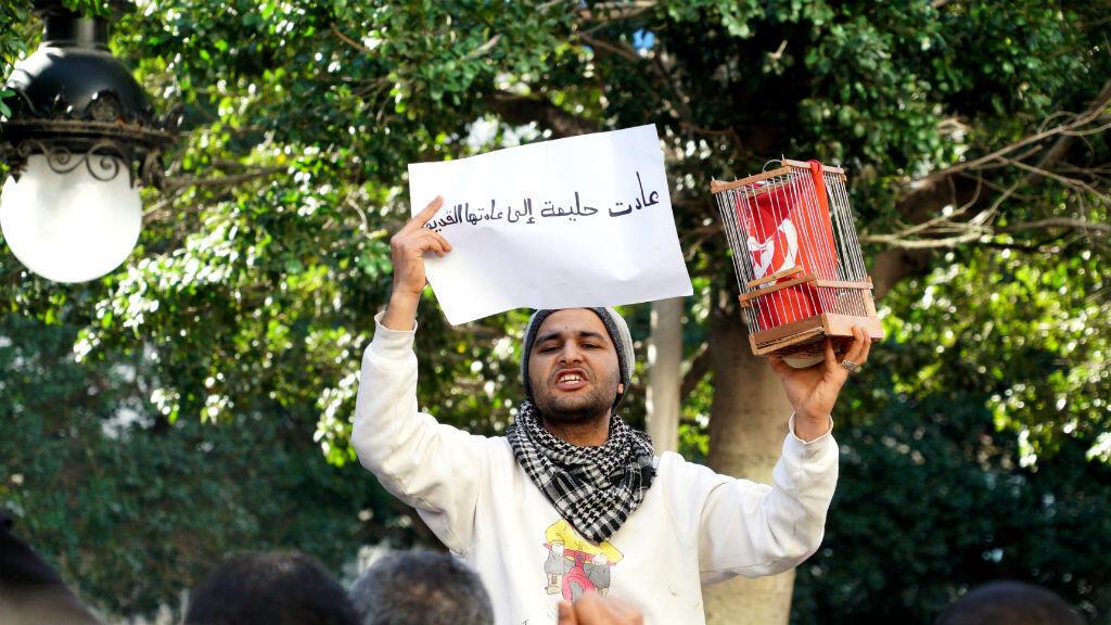 Sur l'avenue Bourguiba à Tunis, un homme a mis un drapeau en cage, dimanche 14 janvier, en symbole de la Tunisie du temps de Ben Ali.