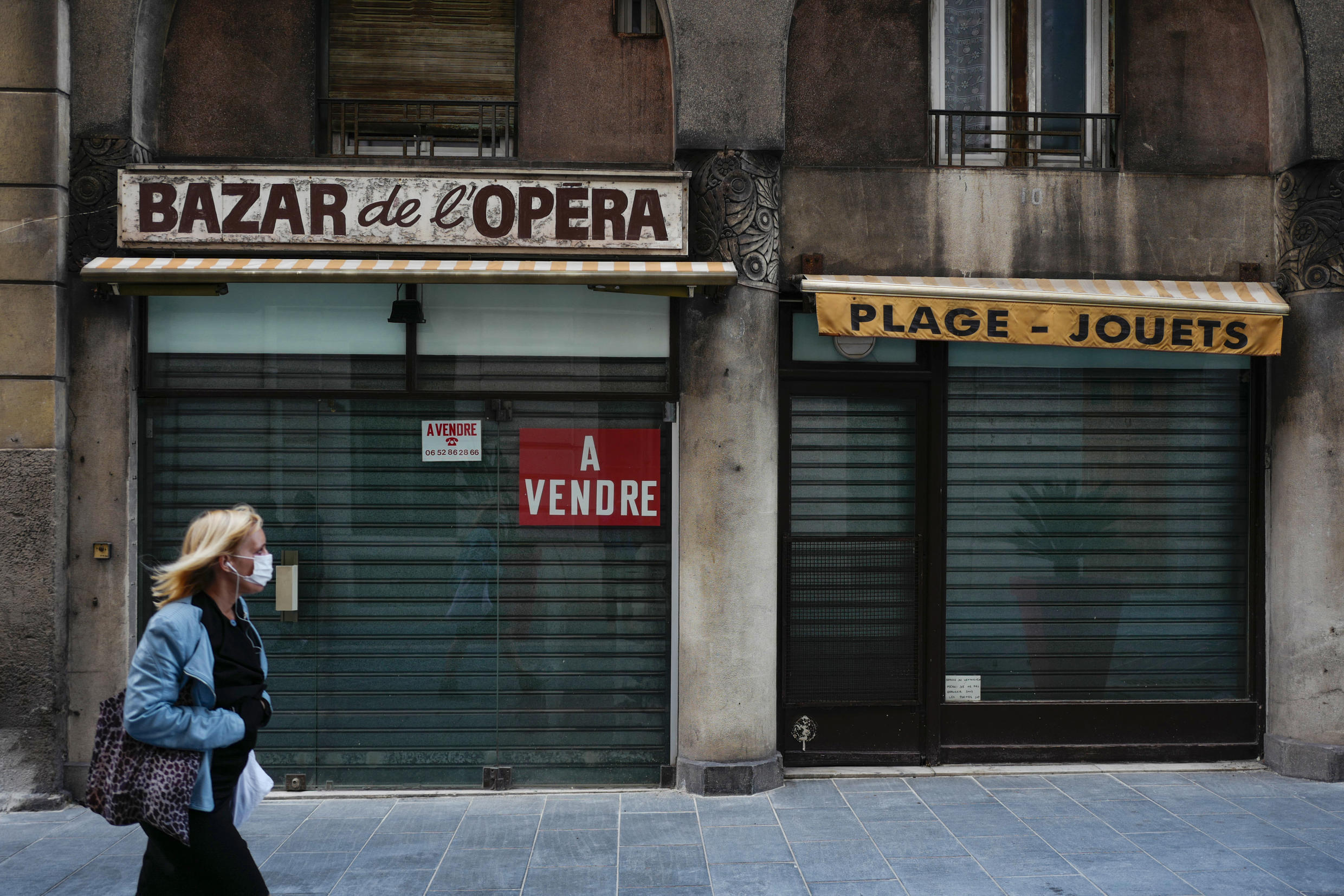 """File photo from April 28, 2020: a woman walks past a closed shop with a """"for sale"""" sign in the city of Nice in southern France on the 43rd day of the country's Covid-19 lockdown."""