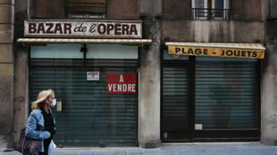 "On April 28, a woman walks past a closed shop with a ""for sale"" sign in the city of Nice in southern France on the 43rd day of the country's Covid-19 lockdown."