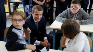 الرئيس الفرنسي يجلس لمحادثة تلاميذ أثناء زيارة لمدرسة مع بداية العام الدراسي في فرنسا في 4 أيلول/سبتمبر 2017