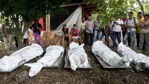 Local people look at the corpses of the five soldiers killed by the FARC on Friday.