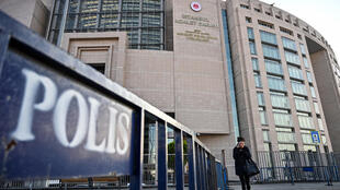A woman walks in front of the courthouse in Istanbul on December 11, 2019 during the trial of Metin Topuz, a US consulate staffer accused of spying and attempting to overthrow the government.