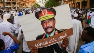 Des partisans soudanais du Conseil militaire de transition (TMC) brandissent une pancarte montrant le portrait du général Abdel Fattah al-Burhan, à Khartoum, le 31 mai 2019.