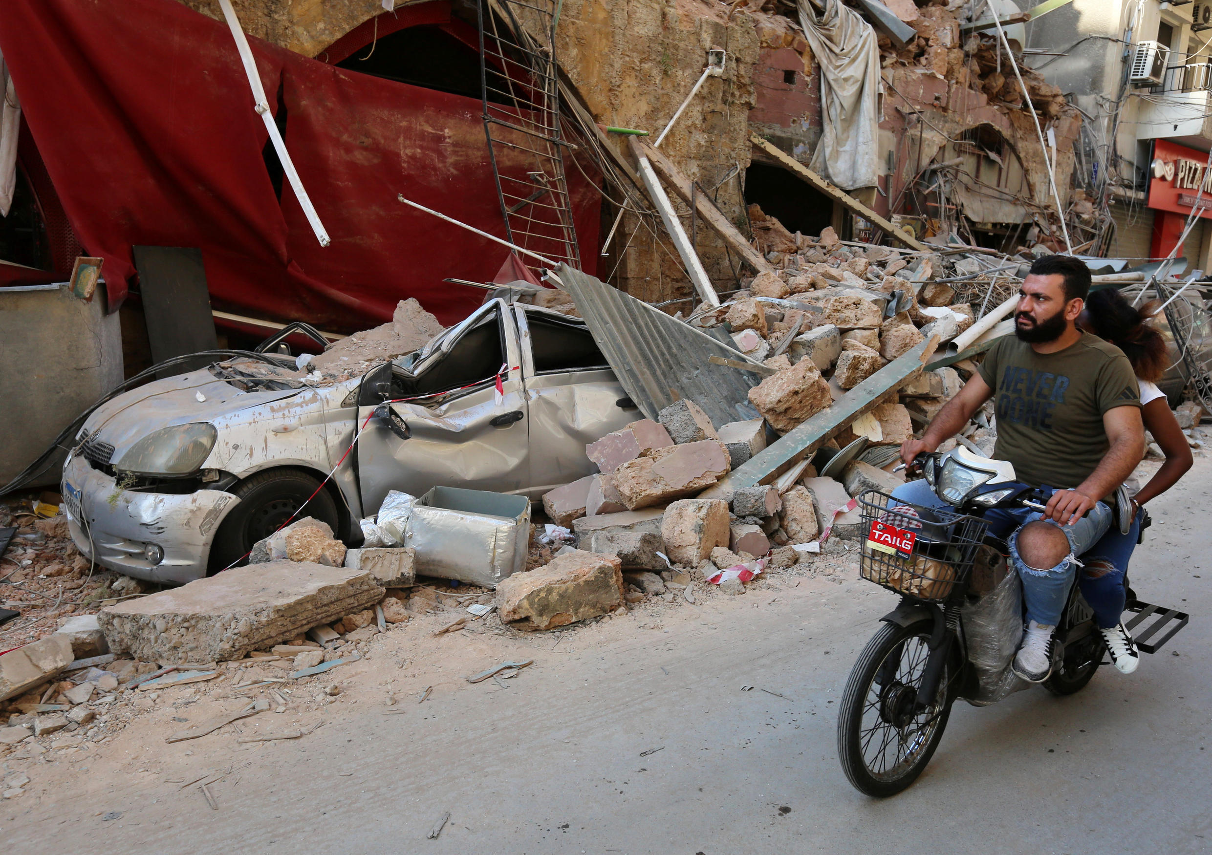 A man rides on a motorbike near rubble from damaged buildings following Tuesday's blast.