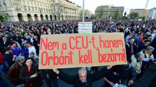 """Un manifestant tient un panneau indiquant """"ne fermez pas la CEU, Orban en prison"""" lors d'une manifestation à Budapest, le 9 avril 2017."""
