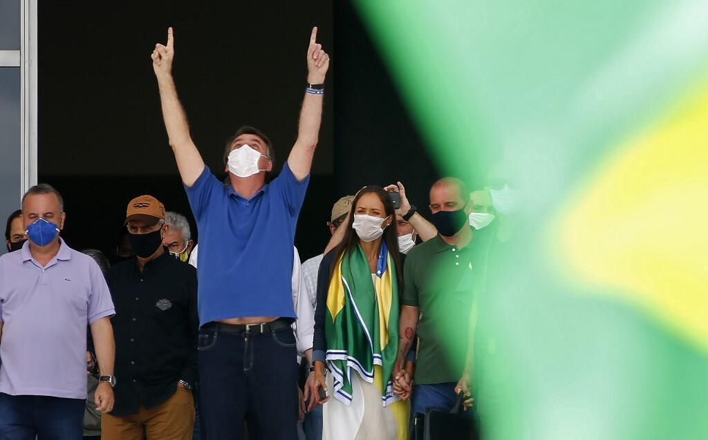 Le président brésilien Jair Bolsonaro harangue ses partisans venus le soutenir devant le palais présidentiel, à Brasilia, le 17 mai 2020.
