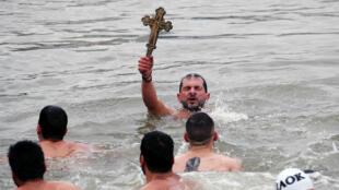 El fiel ortodoxo griego Michalis Vosnauidis enseña el crucifijo sagrado tras nadar en el río Bósforo durante la celebración del Día de la Epifanía en Estambul, el 6 de enero de 2019.