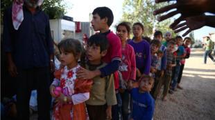 Des enfants font la queue à la Ghouta, à l'est de Damas, pour recevoir des aides d'ONG, le 13 août 2016.